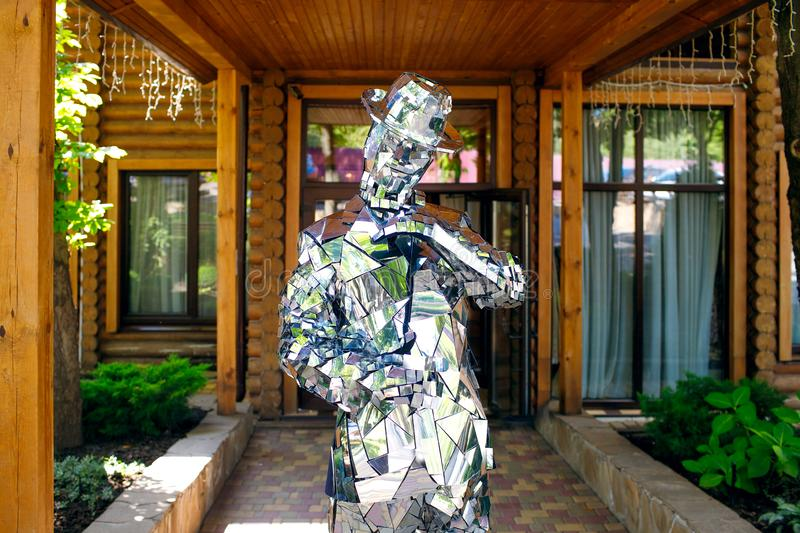 A man in clothes from mirrors poses on a background of wood, brilliant style, disco, beautiful show, mirror man royalty free stock images