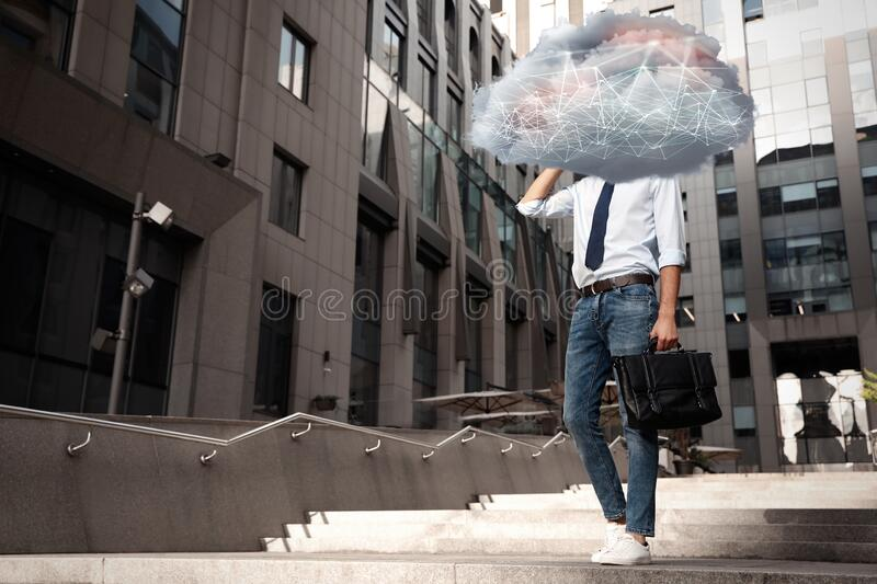 Man with cloud on his head. Modern storage technology concept. Man with cloud on his head outdoors. Modern storage technology concept royalty free stock photography