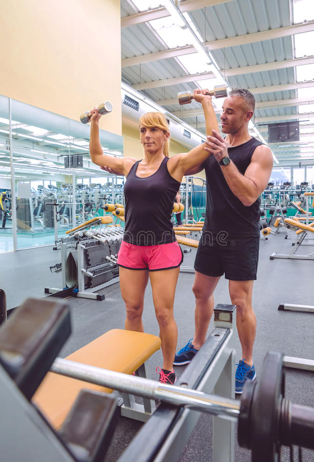 Man coach helping to woman in dumbbells training royalty free stock image