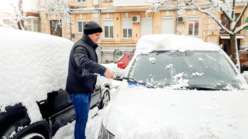 Image of man in coat and hat trying to clean up snow covered car after blizzard with brush against the yellow house royalty free stock photos