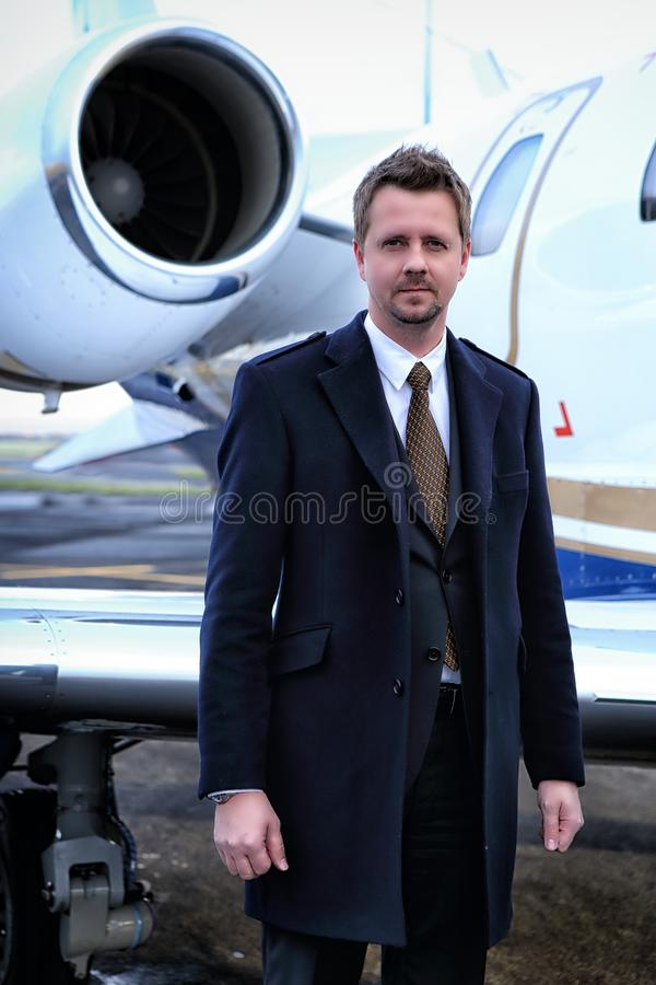 Man in coat by the plane. Man in coat and suit standing by the small jet plane stock images