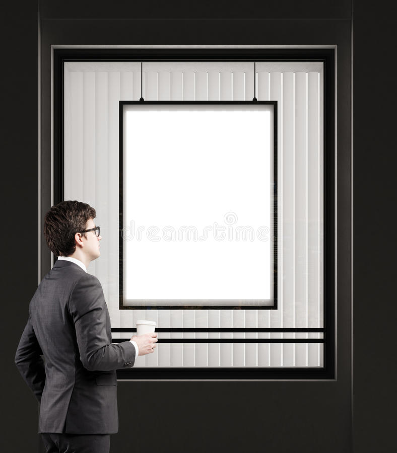 Man with coffee cup standing near a shop window with a framed vertical poster on a black wall stock photos