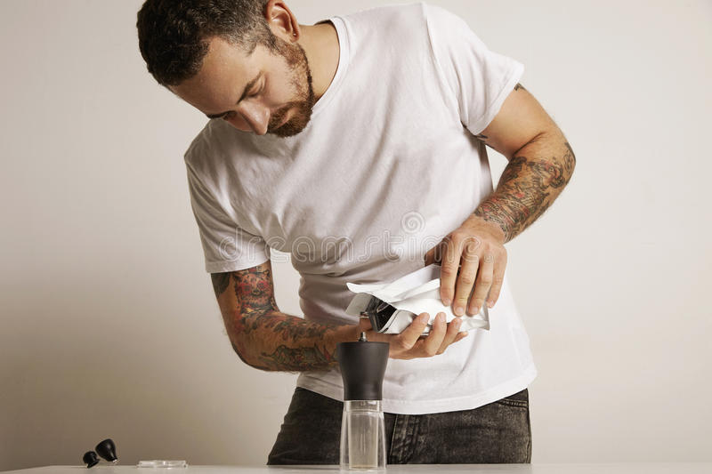 Man with a coffee grinder and bag of beans stock photo