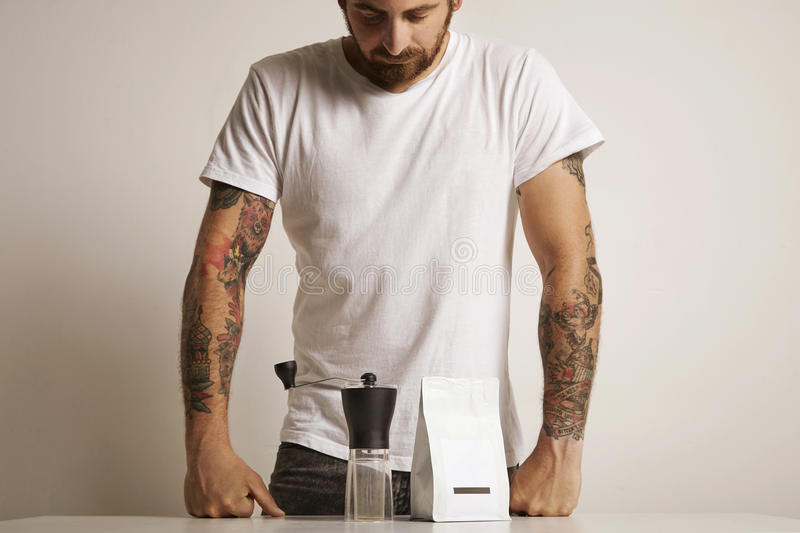 Man with a coffee grinder and bag of beans royalty free stock images
