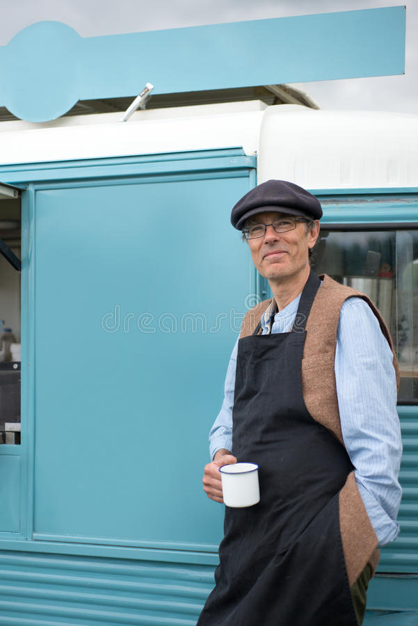 Man with Coffee Mug Standing by a Food Truck stock images