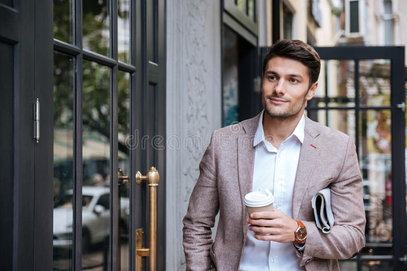 Man with coffee and newsaper walking along street in city royalty free stock photo