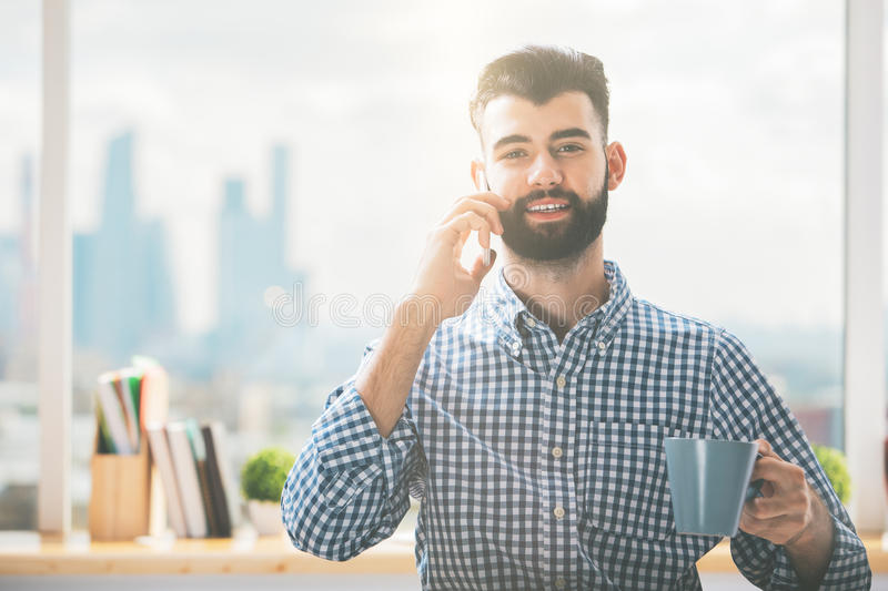 Man with coffee on phone. Handsome young man with coffee cup talking on phone stock photo