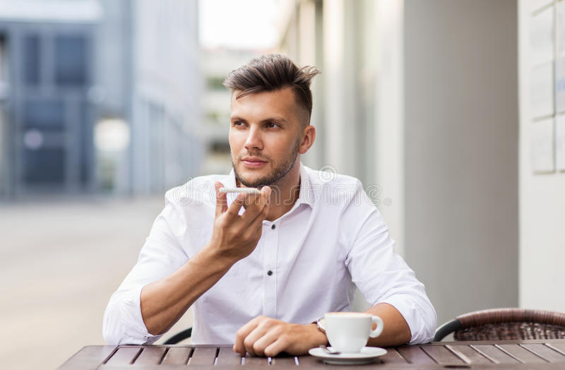 Man with coffee and smartphone at city cafe stock image