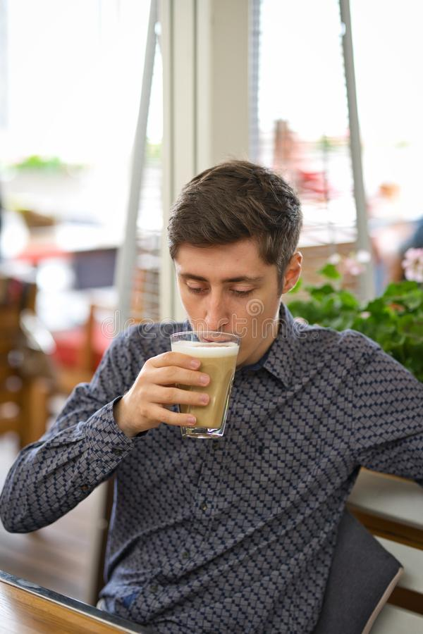 Man drinking large latte at a cafe table royalty free stock photos