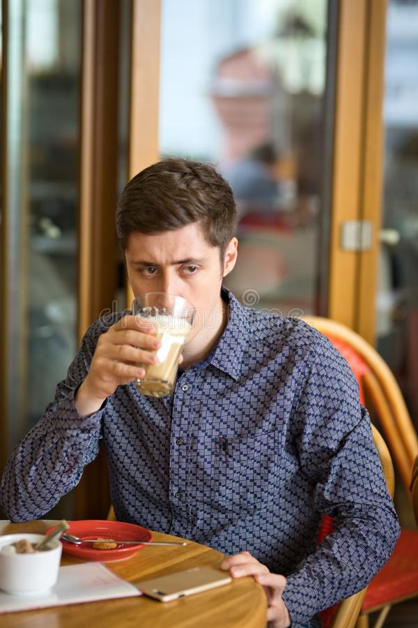 Man drinking large latte at a cafe table royalty free stock images