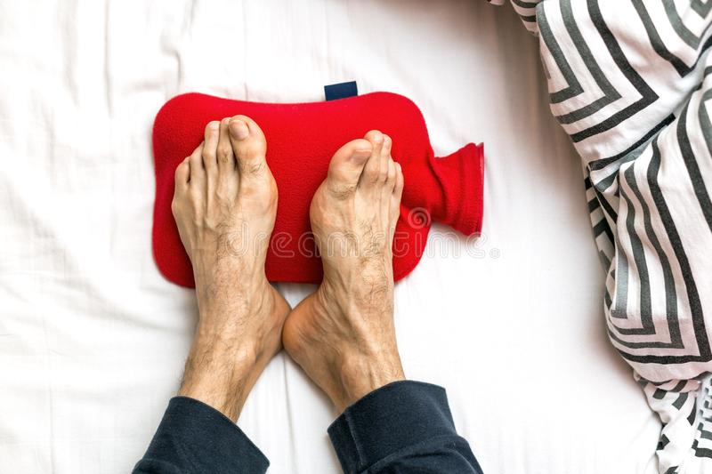 Man with Cold feet in bed on a red hot water bottle. Warming of cold feet royalty free stock image