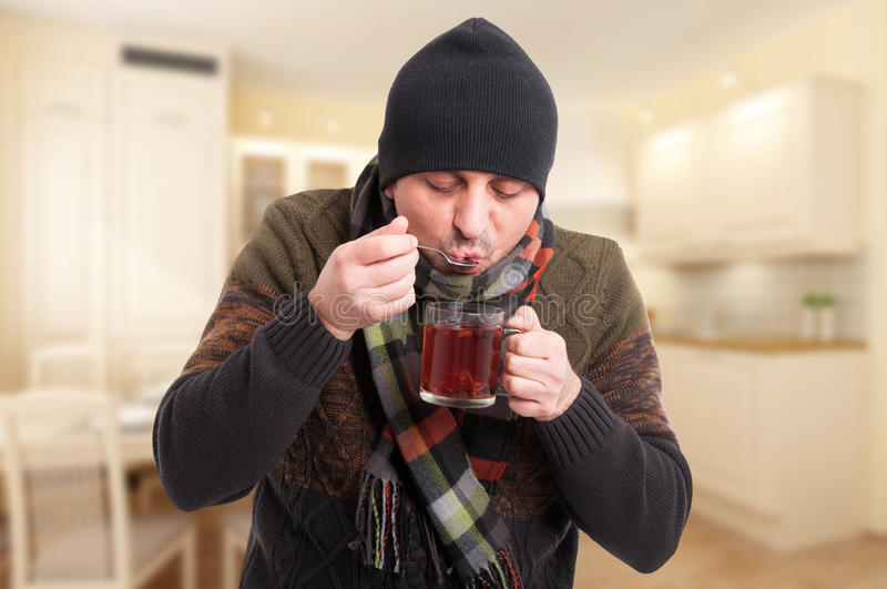 Man with cold or flu drinking hot tea. At his home as illness remedy concept royalty free stock photos