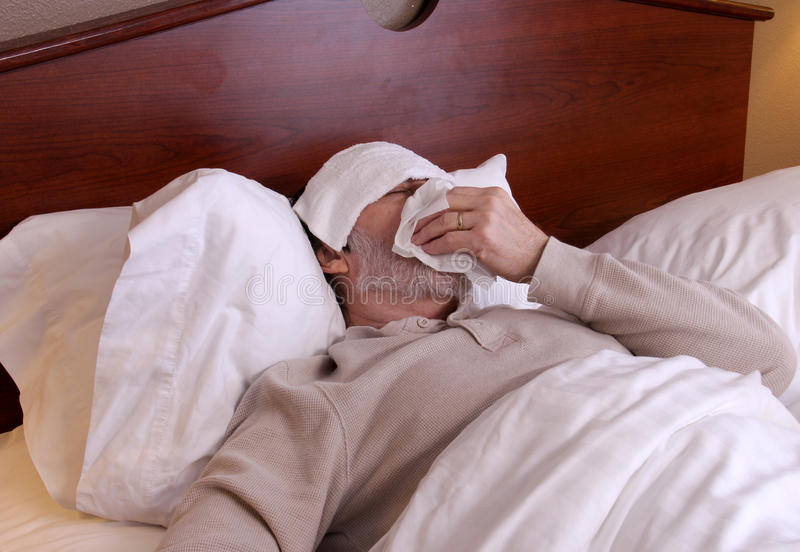 Man with a cold and flu. Man laying in bed with a washcloth on his forehead and blowing his nose stock photo