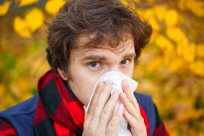 Man with cold rhinitis on autumn background. Fall flu season. Il. L sick sneezing male. Handkerchief, vaccine against influenza virus Caught Cold Headache royalty free stock photos