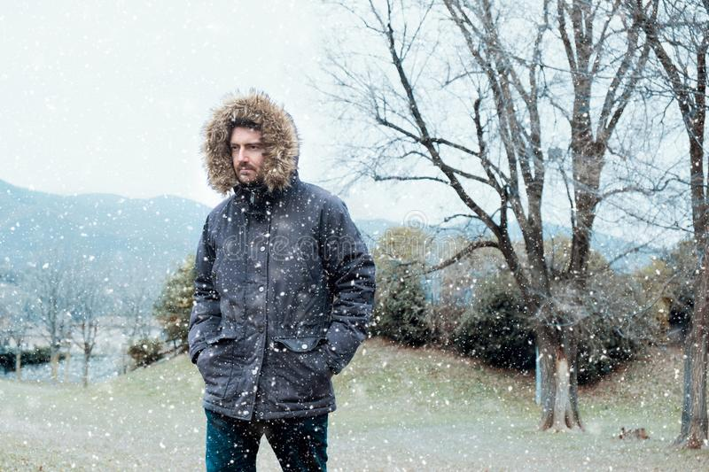 Man in cold and snowy weather storm in winter. Man in winter season and snowy day royalty free stock photo