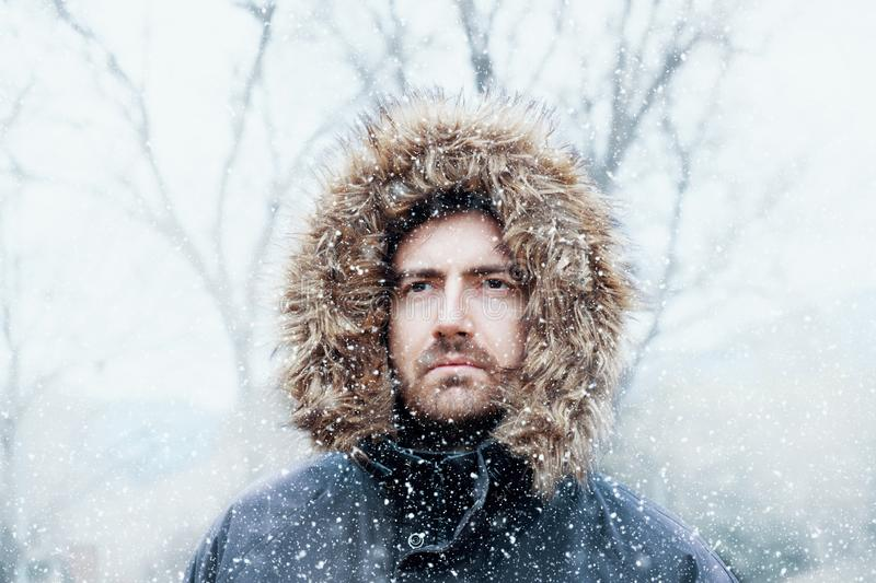 Man in cold and snowy weather storm in winter. Man in winter season and snowy day royalty free stock image