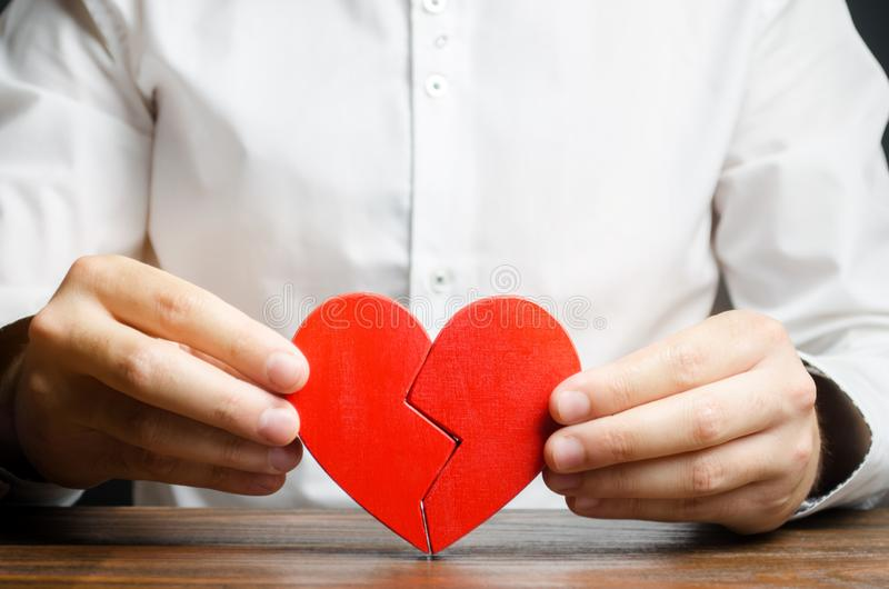 A man collects a broken heart in his hands. Concept of love and relationships. Family psychotherapist services. Reconciliation. stock image