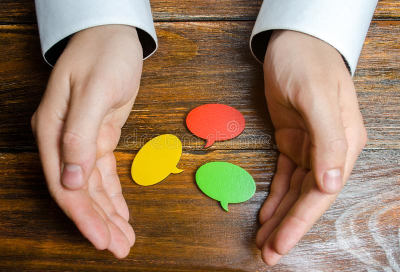A man collects multicolored speech bubbles in his hands. Listen to other opinions and points of view, accepting criticism. And comments. Reverse contact with stock images