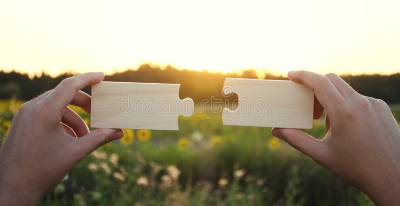 A man collects wooden puzzles at sunset. Concept of success, business solutions. Strategy and goal achievement. Making the right. Decision. Connection and royalty free stock photography