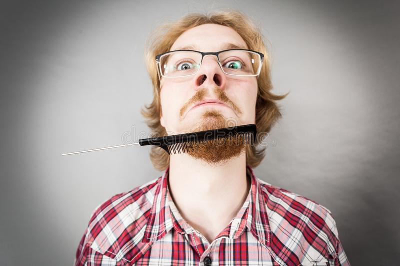 Man combing his beard. Bearded man having trouble with combing his beard using comb brush. Facial hair concept stock images