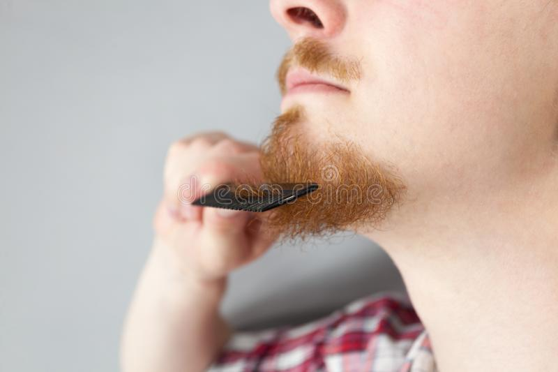 Man combing his beard. Bearded man having trouble with combing his beard using comb brush. Facial hair concept royalty free stock images