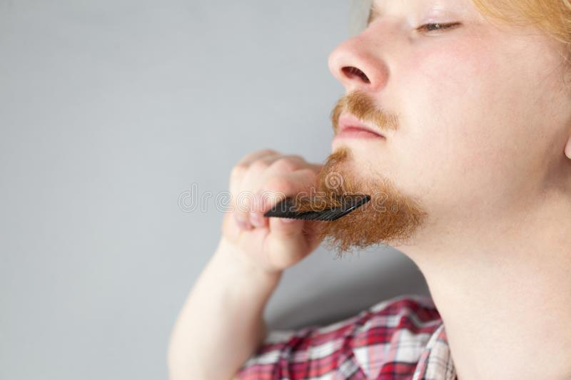 Man combing his beard. Bearded man having trouble with combing his beard using comb brush. Facial hair concept royalty free stock photo