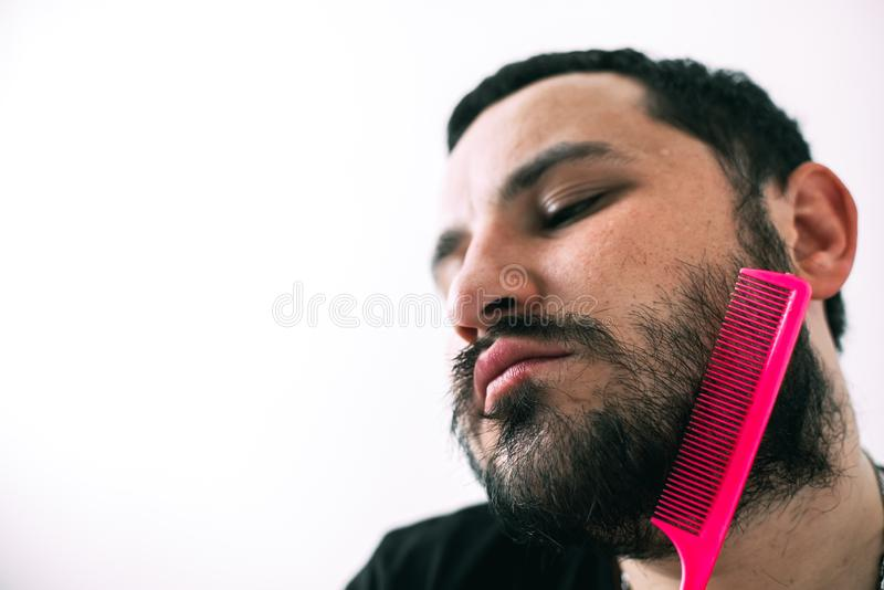 Man combing his beard with a pink comb. Brutal man with glasses combing his beard with a pink comb stock image