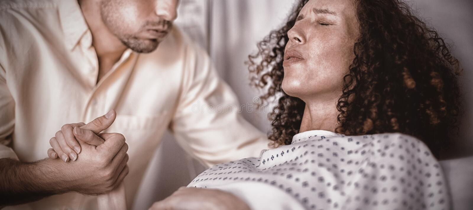 Man comforting pregnant woman during labor in ward stock photography