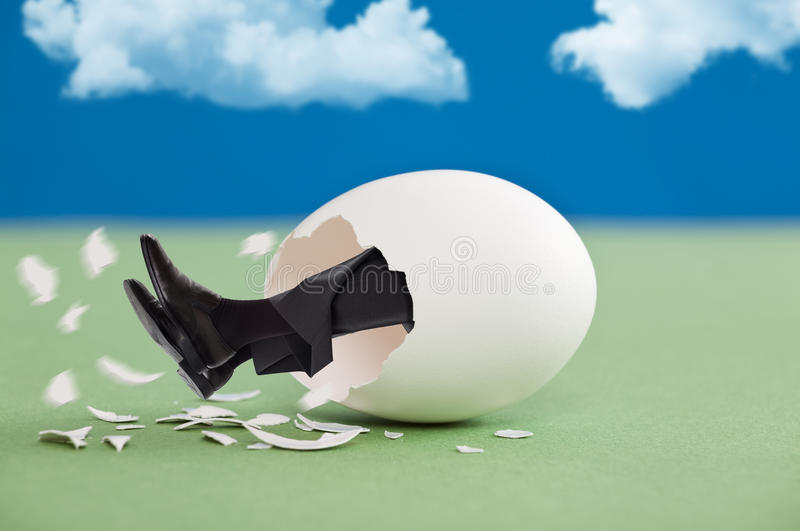 Man coming out of an egg. Feet first royalty free stock photos