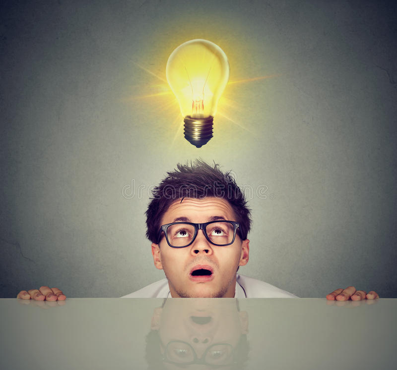 Man coming out from under the table looking up at light bulb above head royalty free stock photos
