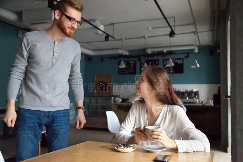 Man coming to cafe table getting acquainted with beautiful woman. Young men coming to cafe table getting acquainted with beautiful women he liked, millennial royalty free stock photo