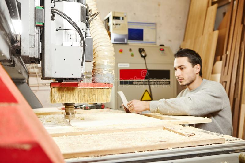 Man compares the CNC machine with the drawing. Device with numerical control. Woodworking industry royalty free stock photos