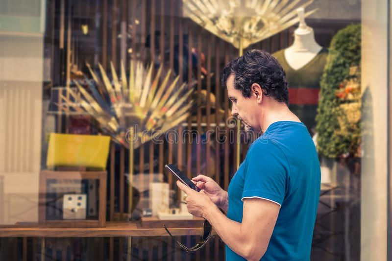 Man comparing prices with his mobile phone in a shop window. Man using smartphone to compare prices in a showcase store stock image