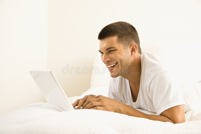 Man on computer. Handsome Caucasian mid adult man lying in bed with laptop royalty free stock photo