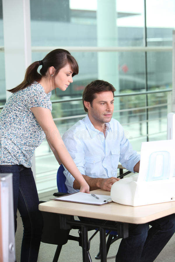 Man at computer with colleague. Man at computer with young female colleague stock images