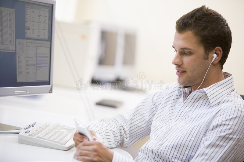Download Man In Computer Room Listening To MP3 Player Stock Photo - Image: 5707956