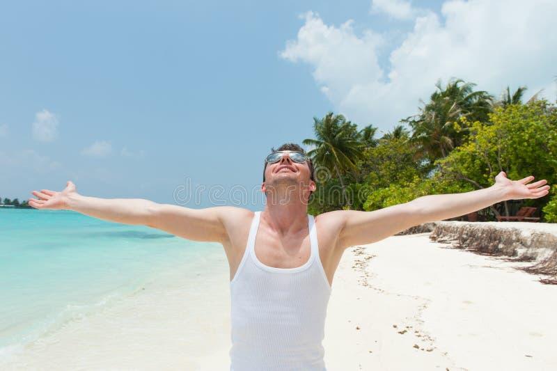 Man con a braccia aperte sopra l'isola della spiaggia immagini stock libere da diritti