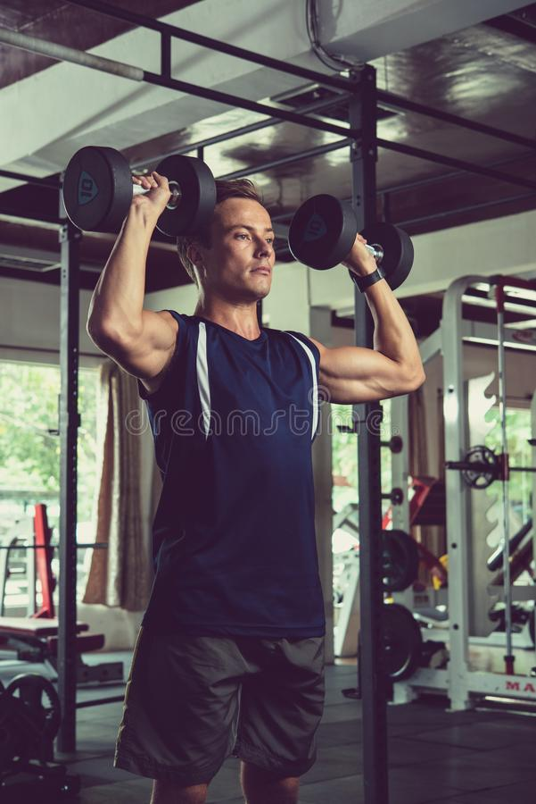 Man concentrated on doing exercises. Fit sporty man concentrated on doing exercises with dumbbells in front of mirror in gym royalty free stock images