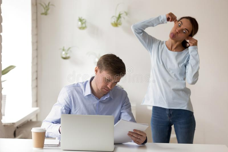 Man concentrated on work near female making funny face. Man sitting at desk working focused on document reading, on background standing mixed race female making royalty free stock photography