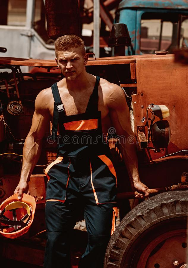 Man concept. Handsome man empoyee rest at tractor cabin. Confident man worker at backhoe loader. Strong man in working. Uniform at heavy construction machine stock image