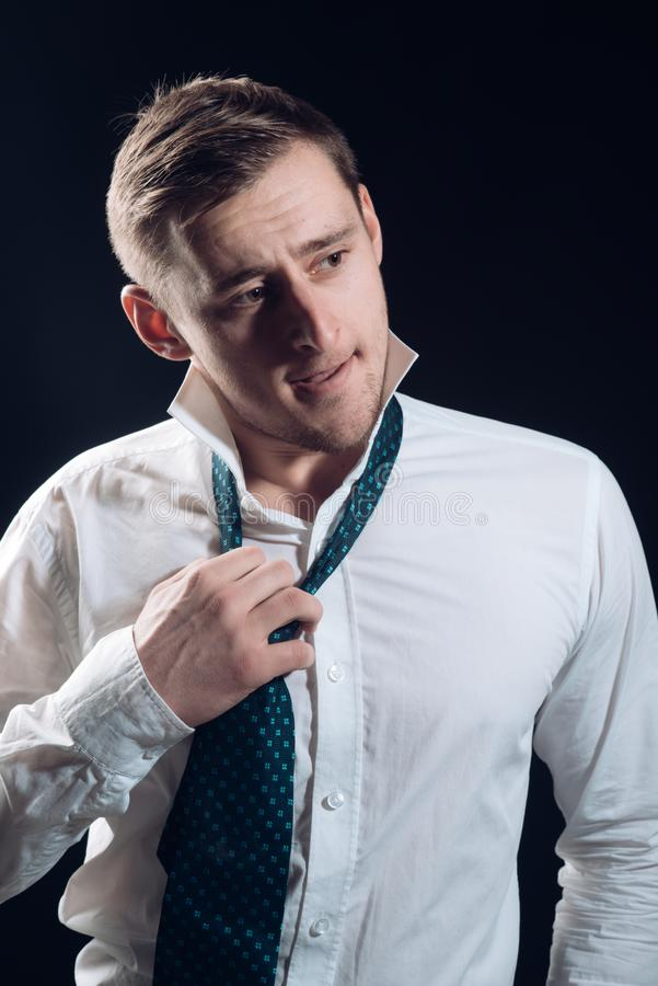 Man concept. Handsome young man. Business man untying tie. Man with blond hair and unshaven face.  stock photo