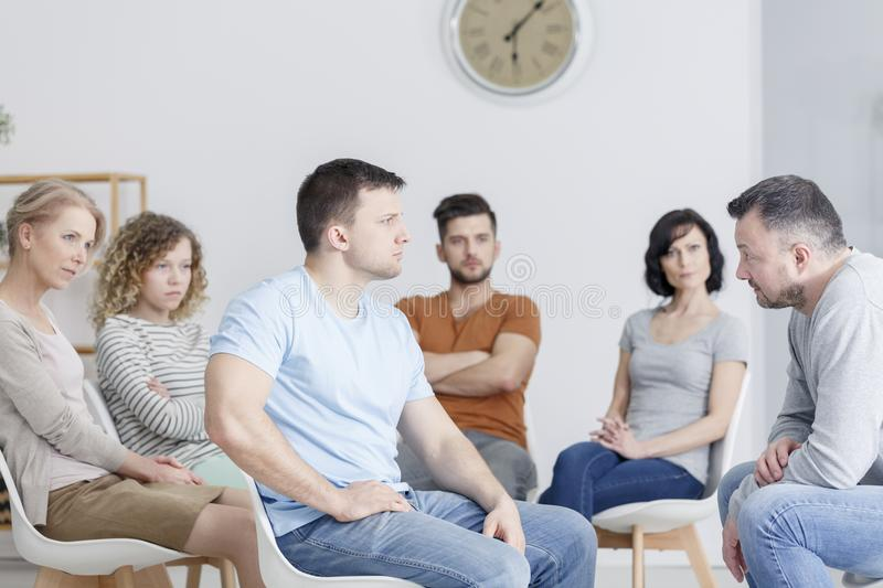 Man confronting father in therapy. Angry young men sitting in a chair and confronting his father in group therapy royalty free stock images