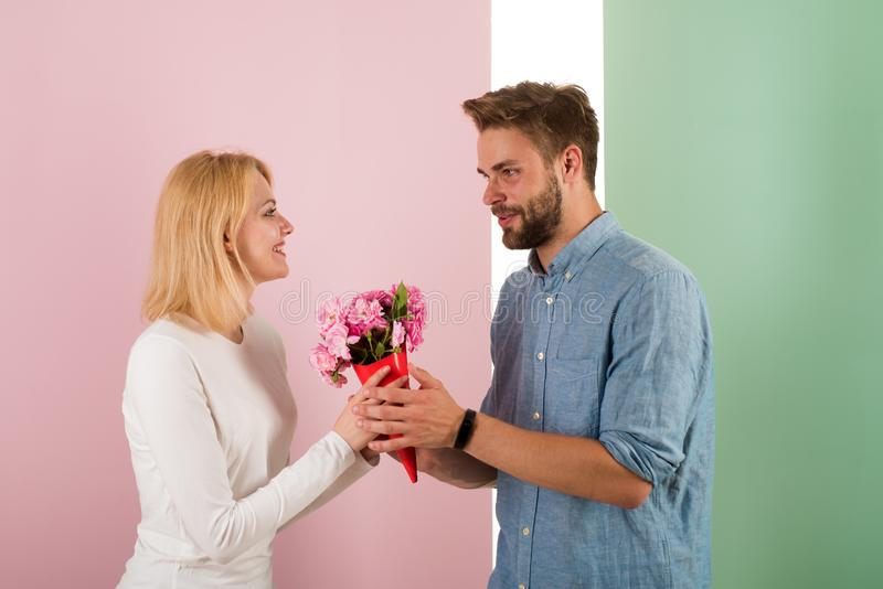 Man congratulates woman birthday anniversary holiday, pastel background. Gift concept. Man gives bouquet flowers to stock images