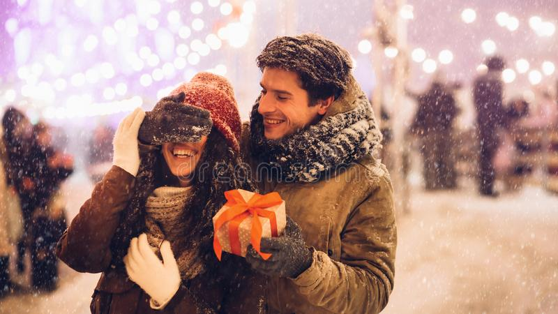 Man Congratulating Girlfriend Giving Christmas Gift Standing In City, Panorama stock photography
