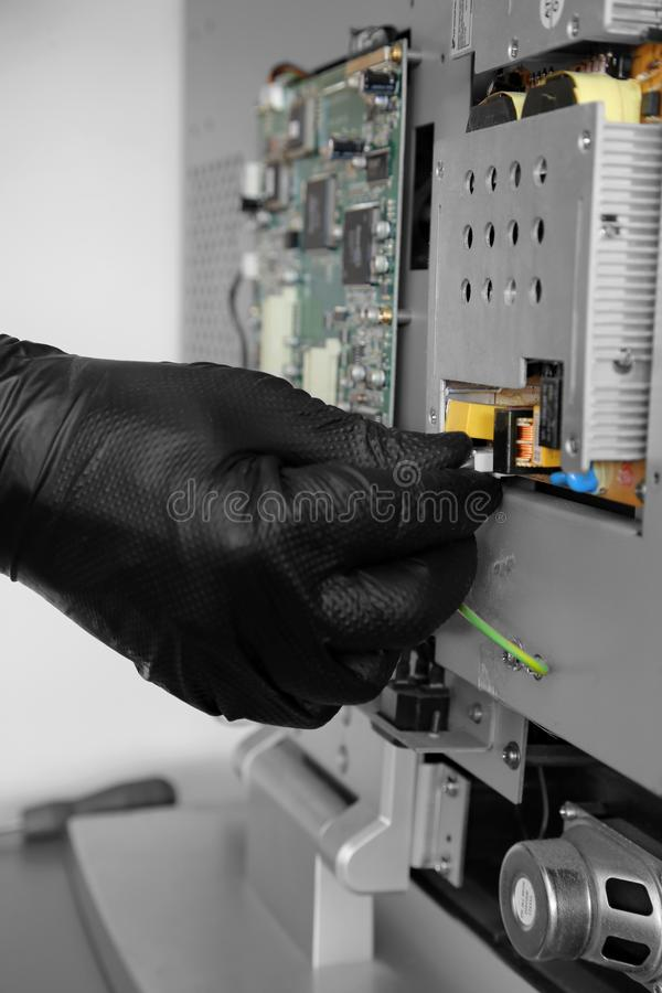 Man connecting a cable onto a circuit board on a television royalty free stock images