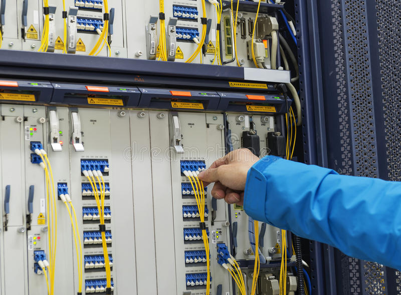Man connecting network cables to switches in the computer room. Man connecting network cables to switches stock photo