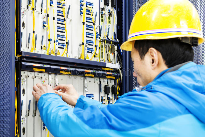Man connecting network cables to switches in the computer room royalty free stock images