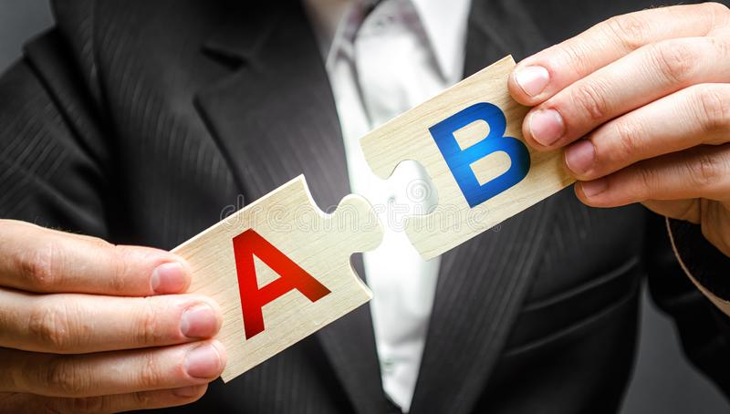 A man connects puzzles with the letters A and B. A/B test marketing research method. multivariate testing. Improving products. And services based on statistics stock photos