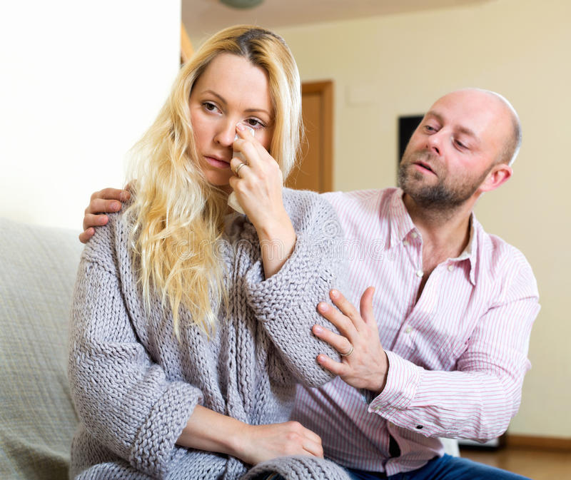 Man consoling woman. Man asking for forgiveness from sad woman royalty free stock photography
