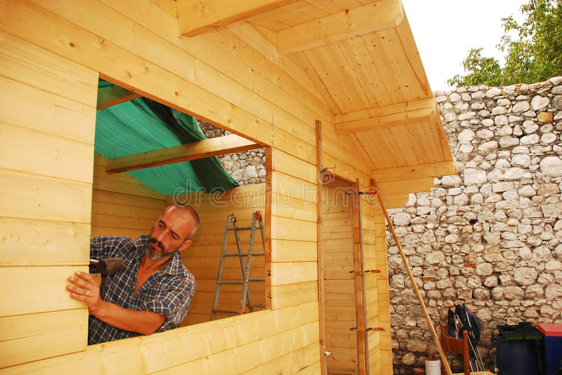 Man Constructing Wooden Cabin stock images